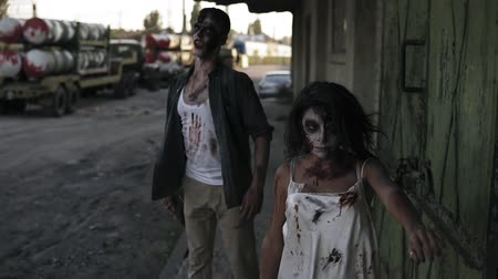 costumes : Halloween horror filming concept. Picture of creepy male and female ghost or zombie walking with wounded face and bloody clothes. Industrial, abandoned town and tracks on the background