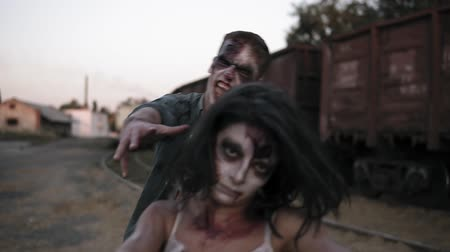 traje de passeio : Portrait of a female zombie with wounded face in bloody dress shouting and zombie man behind her coming on . Abandoned town and railway wagons on the background