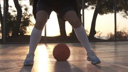 streetball : Close up footage of a female athlete legs in white golf socks and sneakers. Female baasketball player bouncing ball from hand to hand., practicing cross legs exercise. Sun shines on the background