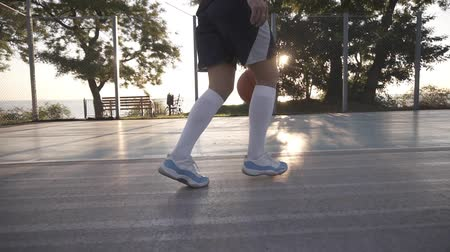 streetball : Close up footage of a female athlete legs in white golf socks and sneakers. Female baasketball player bouncing ball from hand to hand. Sun shines on the background