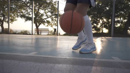 slintání : Close up of a female basketball player in white golf socks and blue and white sneakers training outdoors on the court, bouncing a ball. No face. Close up Dostupné videozáznamy