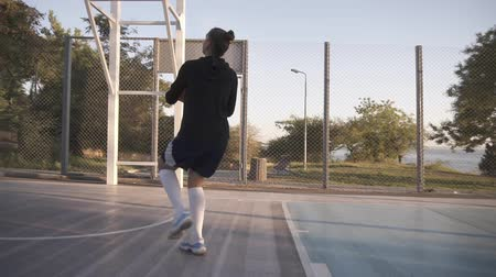 cíle : Low angle footage of a proffesional female basketball player in action. Girls practicing outdoors on the court, throwing a ball to the net. Backside view Dostupné videozáznamy