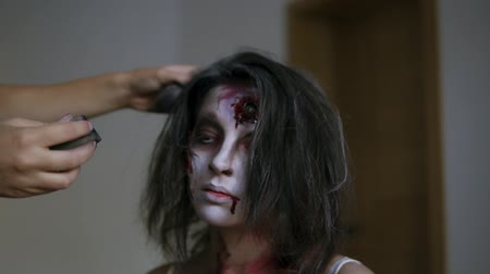 muertos : Make up artist colouring hair of her brunette halloween with silver paint, completing her creeepy image of zombie for Halloween. Close up Stock Footage