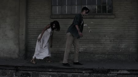 殺人者 : Halloween horror concept. Picture of creepy male and female ghost or zombie walking with wounded face. An old abandoned house on the background. Side view