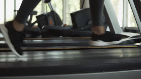 bum : Closeup footage of womans feet in snakers running on a treadmill in fitness club. Blonde woman in grey leggings and sport bra working out at gym