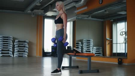lift ups : Sportive, blonde woman exercising in fitness club doing one leg sit ups while holding blue coloured dumbbells. Side view Stock Footage