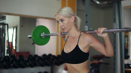 squat : Portrait of a young attractive blonde girl in black bra sit ups with barbell. Female successfully practices workout and crossfit training at gym