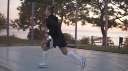 hoop : Close up footage of a young girl basketball player training and exercising outdoors on the local court. Dribbling with the ball, bouncing