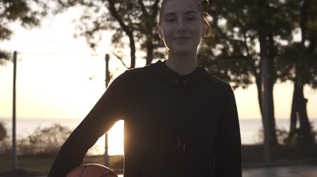 skarpetki : Footage from down and up below a full length of a young female basketball player in hoodie and shorts standing on a local basketball court with ball in her hand. Morning time Wideo