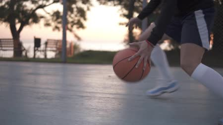 streetball : Close up footage of a young girl basketball player training and exercising outdoors on the local court. Wearing sportswear and white socks, sneakers