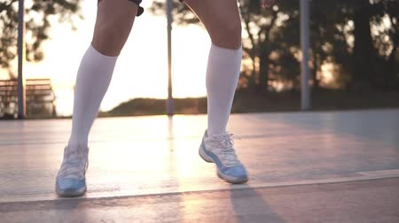 abroncs : Close up of female basketball player legs in white golf socks doing dribbling exersice very quickly, run backwards, training outdoors on the local court. Sun shines on the background