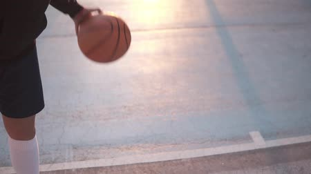 basketbal : Female basketball basketball player bouncing the ball. Slow motion shot of basketball player training on the outdoors court. Morning sun shines on the background