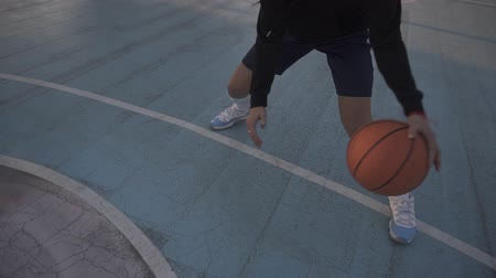 abroncs : Female basketball player in shorts and white socks on professional court running with ball and successfully thowing ball to the net. Handhelded footage. Outdoors