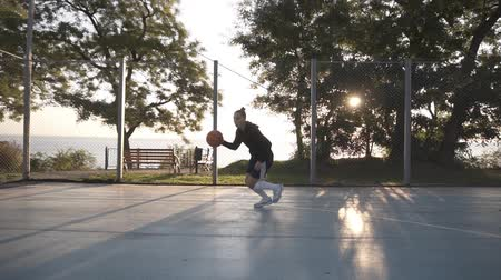 skarpetki : Side footage of a young girl basketball player training and exercising outdoors on the local court. Dribbling with the ball, bouncing and make a shot