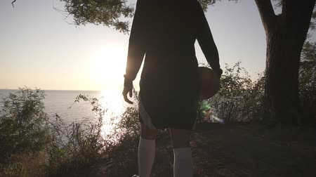 basketbalveld : A basketball player girl comes with a ball in her hand, coming up to the slope with trees around. Looks at the sun shining over the sea. Sea view. Backside view