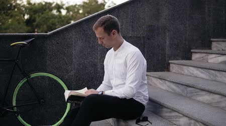 задумчивый : Young serious caucasian man reading book, sitting on city urban stairs, studying or reading, leisure time in city park. Side view