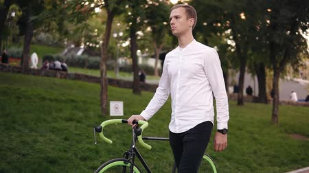 задумчивый : Caucasian young man in white shirt walking with bicycle on the street in town. Rolling his trekking bike while walking by park thoughtfully
