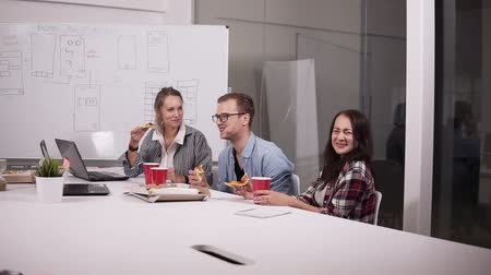 барахло : Young caucasian coworkers having lunch break eating pizza together in office. Laughing, talking, having fun. Staff members recreating after finishing tasks, brainstorm while eating