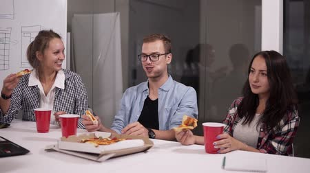 faminto : Young caucasian coworkers having lunch break eating pizza together in office. Laughing, talking, having fun. Food, business lunch and people concept - happy creative team eating pizza at office Vídeos
