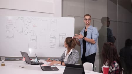 экономический : Young man in glasses and two women sitting at the office table in creative workplace. Brunette woman pointing on whitesheet board, sharing her vision. Man got up and continue to explaine near the board