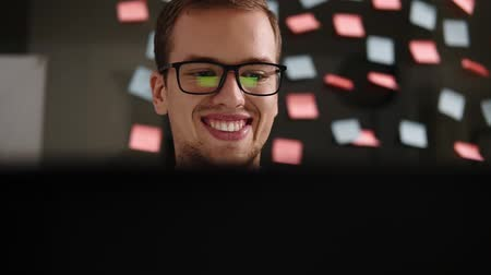 çıkartmalar : Young smiling man in glasses working at a laptop in the office. Businessman - office worker. Male student work at a computer. Search for information on the internet while sitting back to the glass wall with colored stickers on it. Close up