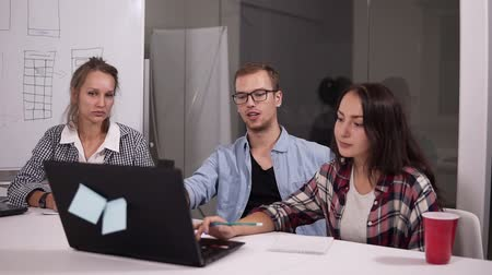 экономический : Making great decisions. Young man in glasses gesturing with a pencil and discussing something with his coworkers listening to him sitting at the office table in creative workplace Стоковые видеозаписи