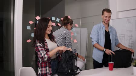 verimlilik : Group of positive young people smiling while come to work to office together with bags and papers standing back to glass wall with sticky colorful papers. Slow motion Stok Video
