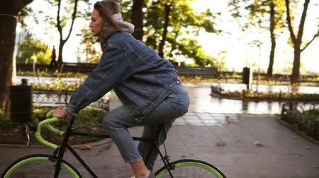 мощеный : Beautiful woman riding bike on city paved road. Woman bicycle rider have a ride in the morning in the park. Lens flares on the background Стоковые видеозаписи