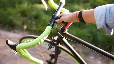 aimed : Aimed top view footage of a young woman walking besides a bicycle in the morning park or lawn. The girl walking with her trekking bike, holding with a green coloured rudder Stock Footage