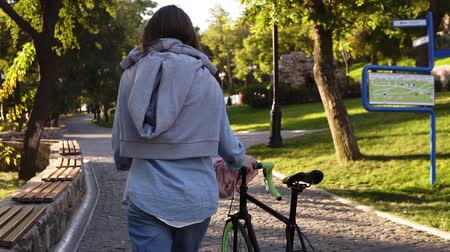 nem városi színhely : Beautiful, young joyful woman walking besides a bicycle in the morning park. The girl walking with her trekking bike, holding with a rudder with a hoodie on her back, smiling. Trees and sun shines, local green park Stock mozgókép