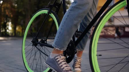 мощеный : Close up footage of a young girl in jeans and sneakers starting riding her trekking bike with green wheels, pushing pedals. City side, lens flares, no face. Unfocused background Стоковые видеозаписи