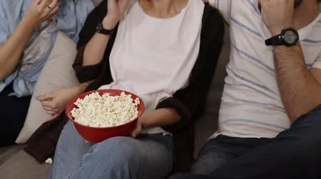 afetuoso : Aiming footage of a big red bowl with popcorn. Friends are gathering together and having fun at the living room, grabbing a popcorn from a bowl