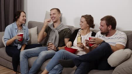 sobremesa : Friends are gathering together and having fun at the living room with loft interior. Male and female company, The girl with a big red bowl with popcorn, everyone drinking beer or soda, laughing, talking