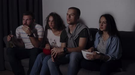 frightful : Four friends eating popcorn, drinking beer watch horror movie together and are very captivated and scared, sit still. Close eyes from scary picture. Movie night