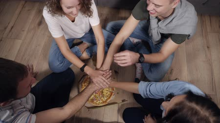 tektura : Top view of young people taking hand to hand under the box with pizza then take slices of hot tasty pizza from cardboard box