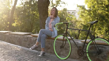 ileri : Pretty girl sitting on the bench or parapet in the city park with her trekking bike next to her. Talking by her mobile phone, smiling. Wearing bright pink and blue coloured casual clothes and sneakers. Trees and sunshine on the background Stok Video