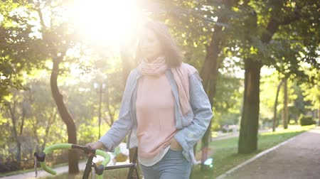мощеный : Front view of a young woman walking besides a bicycle in the morning park. The girl walking with her trekking bike, holding with a rudder. Trees and sun shines on the background. Lens flares