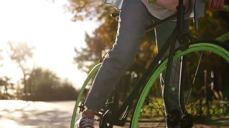 obiektyw : Close up footage of a young girl in jeans and sneakers starting riding her trekking bike with green wheels, pushing pedals. City side, lens flares, no face. Front view