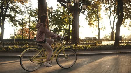 kolo : Pretty little girl riding yellow coloured bike on the street in summer city park. Trees and sunshines on the background