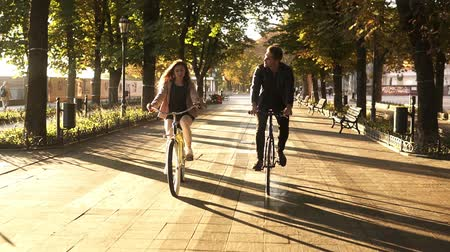 бульвар : Front view of a young couple or friends riding their bikes in the city park or boulevard in summertime. People, leisure and lifestyle concept Стоковые видеозаписи
