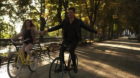 cyclists : Beautiful young couple riding their bikes in the empty city park or boulevard in summertime. Holding hands together while cycling bikes. Front view Stock Footage