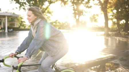 kikövezett : Happy, smiling woman bicycle rider have a ride in the morning in the city street or park. Lens flares on the background, morning dew