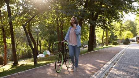 beside : Front view of a young joyful woman walking besides a bicycle in the morning park. The girl walking with her trekking bike, holding with a rudder. Trees and sun shines on the background. Lens flares