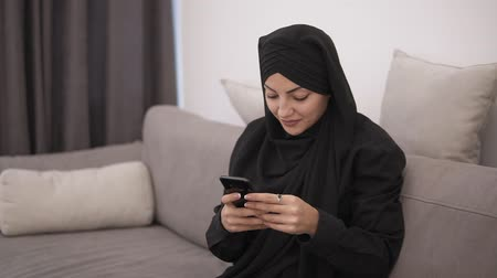 pokrývka hlavy : Beautiful muslim woman in black hijab sitting on the sofa and looking to her smartphone and smiling. Modern lofr interior room with white wall on the background