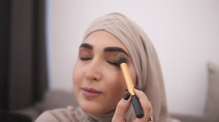 bege : Beautiful muslim woman doing makeup on her face with brush, applying eyeshadows on her eyelid. Wearing beige hijab. Modern life of muslim people. Aim footage of the eyeshadows set
