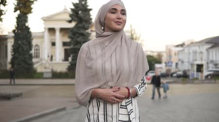 szerény : Confident and attractive woman wearing a hijab. Young woman walking by the city street with beautiful old style buildings and trees on the background Stock mozgókép