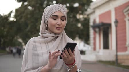 conservative : Muslim beautiful woman in pastel hijab with makeup standing on the street holding smartphone while have a walk in the city. Texting a message
