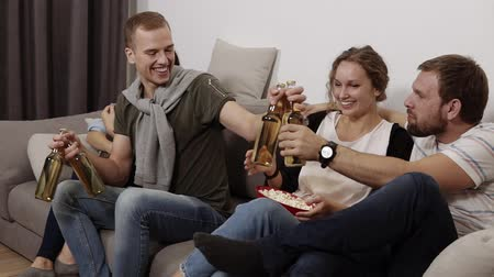 взял : Friendship, communication, party time -group of four are hanging out together - male and female company sitting on a sofa. Young man took some drinks in glass bottles for friends