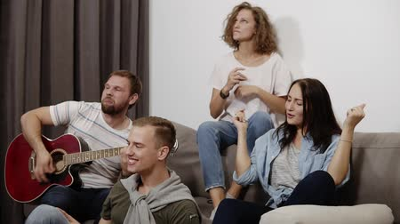 juntar : Happy friends sit around on sofa and listen to guy playing the acoustic guitar. Get together to have a good time with best friends. Feel the music and rhythm, dancing while sitting