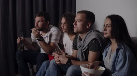 frightful : Best friends eating popcorn, drinking beer watch horror movie together and are very captivated and scared, sit still. Close eyes from scary picture. Movie night Stock Footage